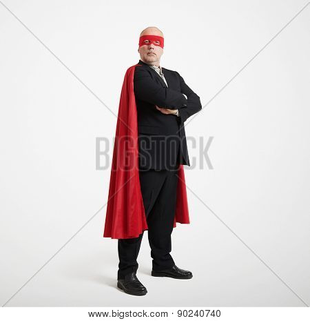 confident senior businessman wearing like super hero in red mask and cloak over light grey background