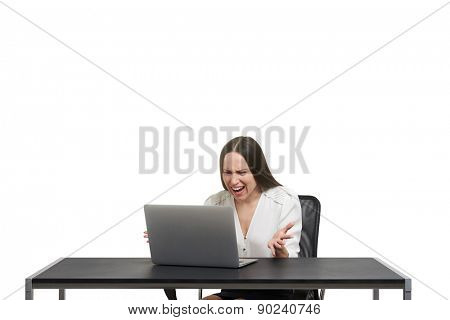 angry screaming woman looking at laptop and spreading her hands over white background