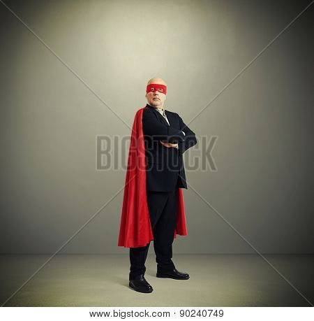assured senior businessman wearing like super hero in red mask and cloak over light grey background