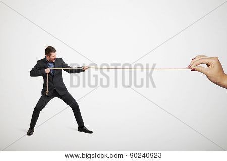 businessman in formal wear and big woman's hand pulling the rope over light grey background