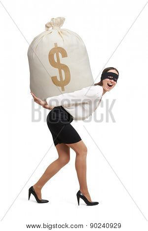 laughing woman in formal wear and black mask on the eyes holding big bag with money and looking at camera. isolated on white background