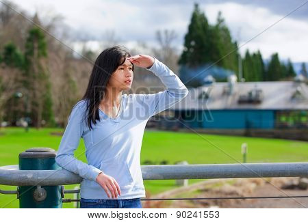 Young Teen Girl Standing, Leaning Against Railing At Park Shading Eyes To Look Off To Side