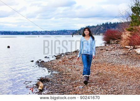 Young Teen Girl Walking Along Rocky Shoreline Of Lake In Early Spring Or Fall
