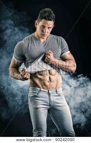 Handsome, fit young man pulling up t-shirt revealing abs