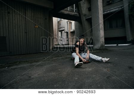 tattooed lady sitting on longboard in backyard