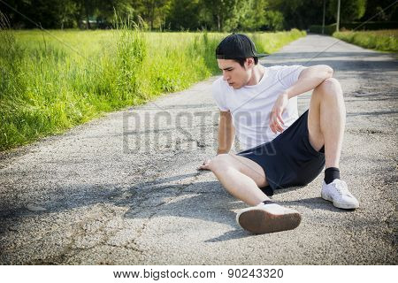 Handsome young man resting sitting on road after running