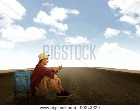 Man Sitting On The Road Using His Cellphone