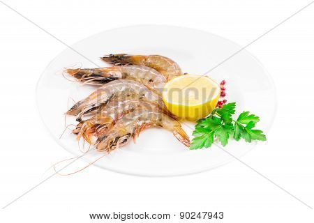 Raw shrimps on plate with lemon.