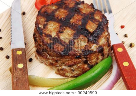 extra thick hot beef meat hamburger lunch on light wooden plate with tomatoes salad and cutlery isolated on white background