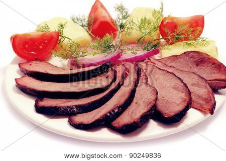 grilled beef meat steak with fried potatoes and tomatoes on white plate isoalted over white