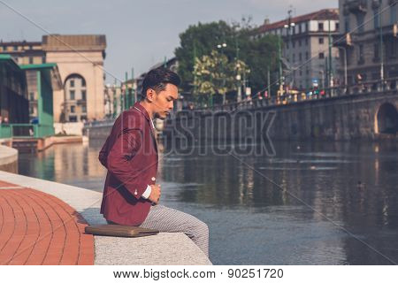 Handsome Asian Model Sitting By An Artificial Basin