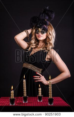 Mysterious Woman In A Mask Near The Table With Alight Candles