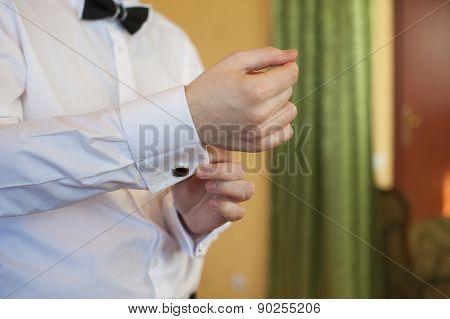 Man Puts Cufflinks On Sleeve White Shirts