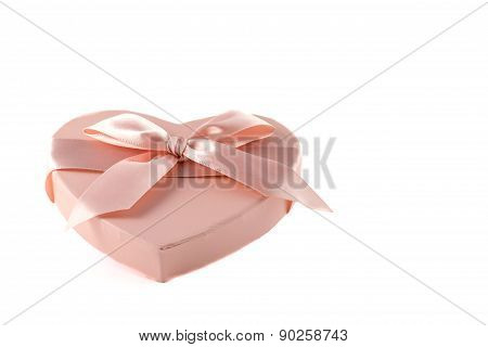 Pink heart-shaped box with purple ribbon knot