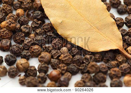Pepper with dry bay leaf isolated on white.