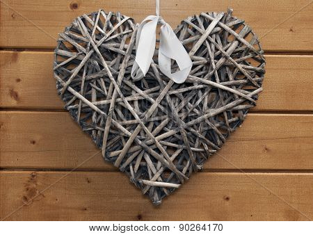 Wooden Heart With White Ribbon On A Wooden Wall