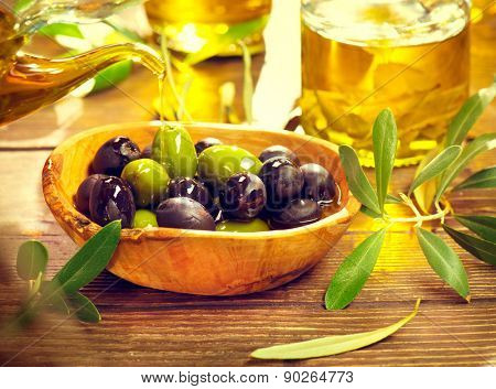 Olives. Green and black olive closeup. Olives and Olive Oil on the wooden table. Healthy food, Mediterranean cuisine