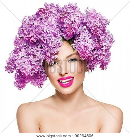 Beauty fashion model Girl with Lilac Flowers Hair Style. Beautiful Smiling Model woman with Blooming flowers on her head. Nature Hairstyle. Summer. Holiday Creative Makeup. Make up. Vogue Style