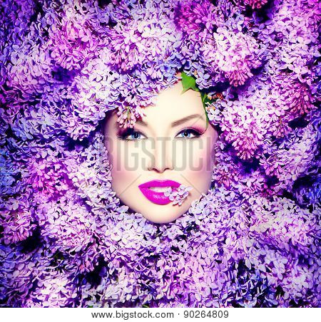 Beauty fashion model Girl with Lilac Flowers Hair Style. Beautiful Model woman lying on Blooming flowers background. Nature Hairstyle. Holiday Creative Violet color Makeup. Purple Make up Vogue Style