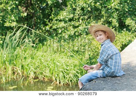 Angling Boy With Wooden Rustic Fishing Rod Sitting On Concrete Bridge