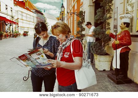 Budapest, Hungary, June 27, 2014 . Two Tourists Looking Map Of Budapest.  Picturesque Street In Buda