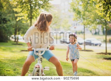 Mother Playfully Riding A Blonde Girl's Bike In A Sunny Park
