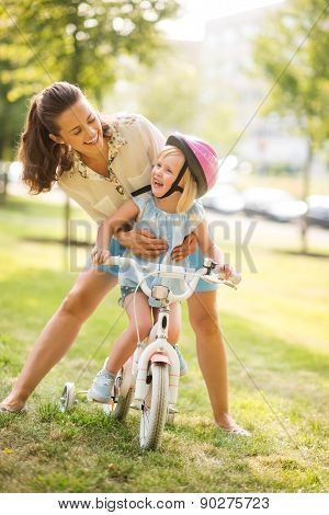 Laughing Mother Holding Daughter On Bike In A Sunny City Park