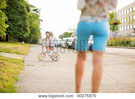Smiling Girl Rides Her Bike On City Sidewalk As Mother Watches