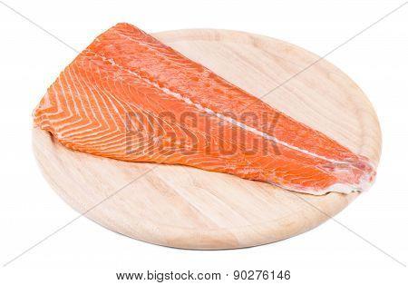 Raw salmon fillet on wood platter.