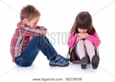 Angry Sulking Children Sitting On The Floor