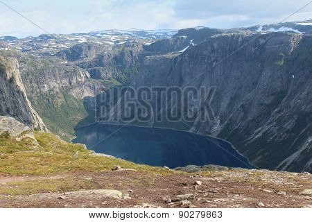 A lake is surrounded the mountains.