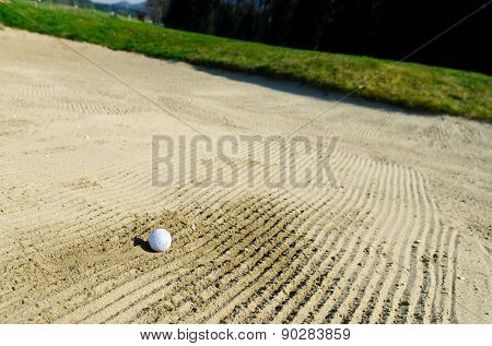 Golf Ball Is Trapped In Sand Bunker