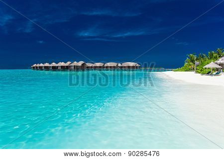 Overwater bungallows in blue lagoon on tropical island with palm trees