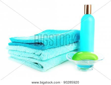 Towels with shampoo bottle and soap isolated on white