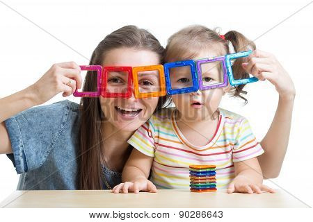 child and mother playing with magnetic constructor toy