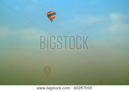 Three Hot Air Balloons Flying Through Morning Fog