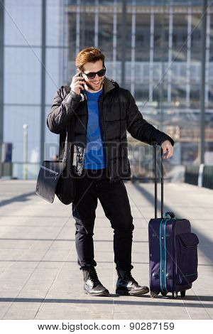 Happy Traveling Man Talking On Mobile Phone At Airport