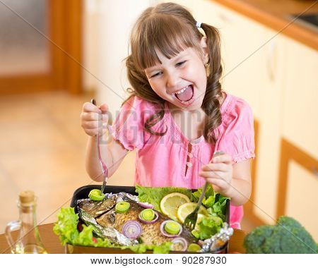 Funny child girl and grilled fish. Healthy eating seafood.