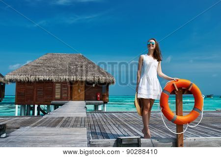 Woman on a tropical beach jetty at Maldives