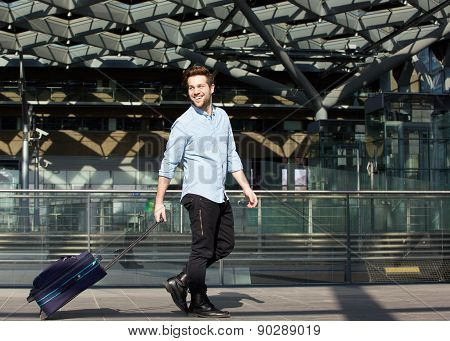 Happy Male Traveler Walking With Suitcase