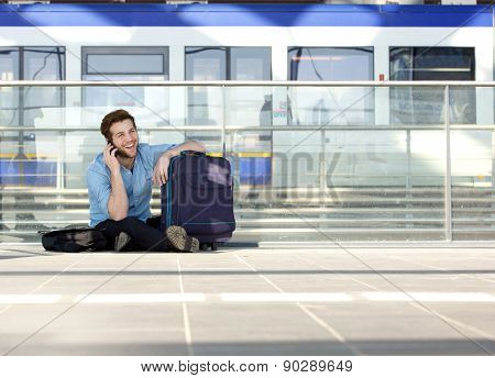Man Sitting On Floor With Bag And Talking On Mobile Phone