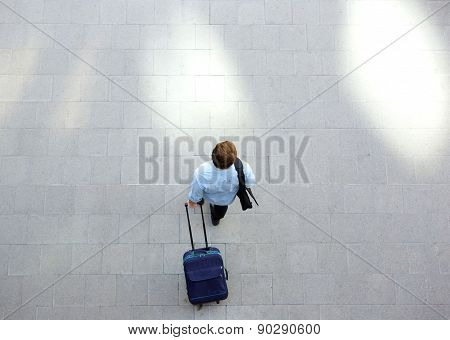 Young Man Walking With Luggage At Station