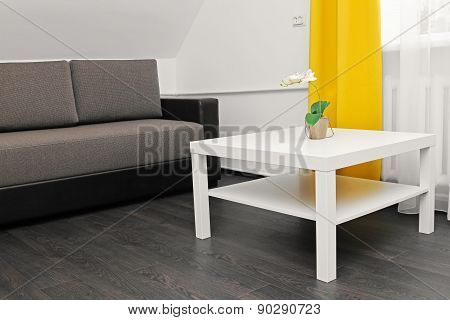 Bright Apartment Interior With Sofa, Coffee Table And Yellow Curtains