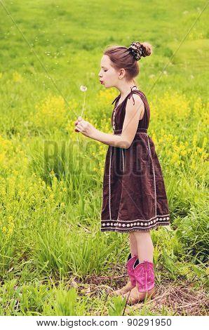 Girl blowing dandelion making wish