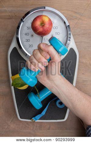 Fresh Apple And Dumbbells Tied With A Measuring Tape On A Weighting Scale