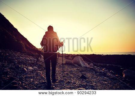 young woman hiker walking on sunrise seaside stone coastal