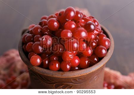 Red cranberries in clay cup on wooden table with scarf, closeup