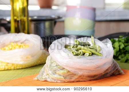 Frozen vegetables in bags on kitchen table close up