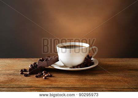 Cup of coffee with grains and chocolate on wooden table on dark background