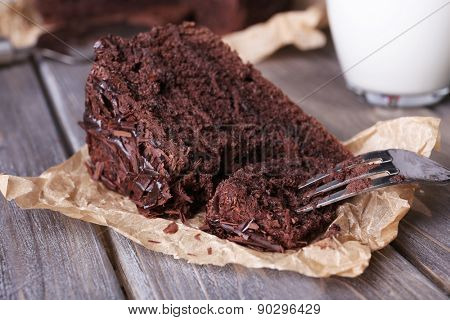 Sliced tasty chocolate cake on sheet of parchment and glass of milk on wooden table background